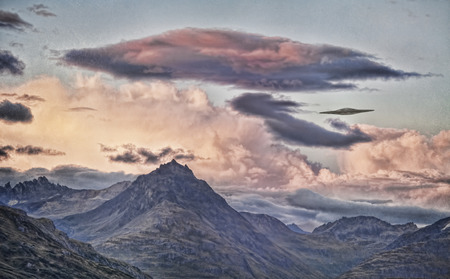 UFO flying saucer over  mountains with sunset clouds processed with textures for an artistic look.