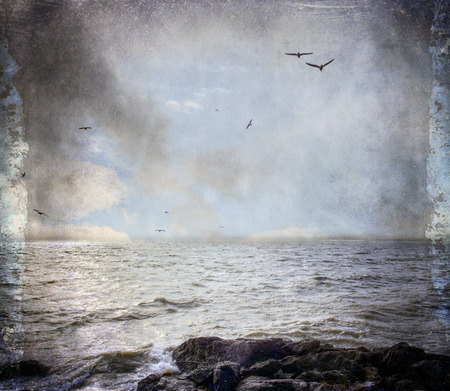 grunge textures: Ocean waves on a rocky shore with gulls flying in the clouds, textures added for a vintage look.