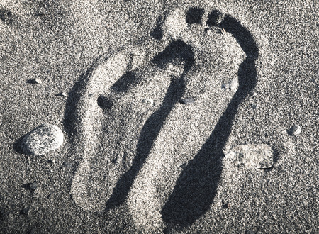 nestled: Footprints in beach sand nestled together like a cozy couple in black and white.