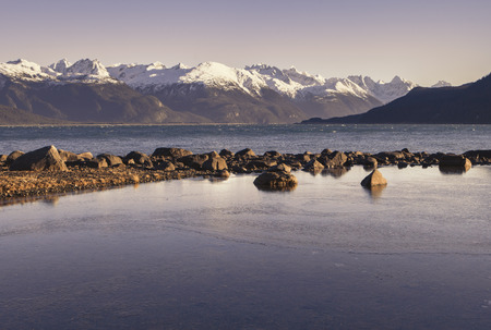 portage: Picture Point near Haines Alaska in evening light with snow covered mountains in the background. Stock Photo