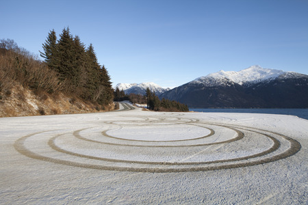 traction: Perfect circles made by tire tracks from testing traction or teenagers showing off.
