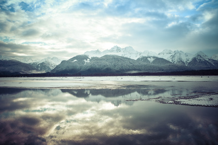 southeast alaska: Mountains reflected in the Chilkat River in Southeast Alaska in winter before freeze-up with artistic coloration added.