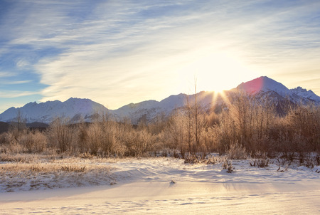 southeast alaska: Winter sunset behind the Chilkat mountains in Southeast Alaska with light snow on the ground. Stock Photo