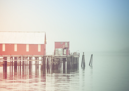 Old Alaskan cannery on a foggy day with coloration for an artistic look. Stock Photo