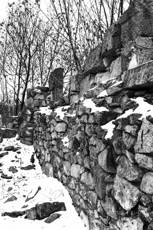 stark: Remains of an old stone building in winter in stark black and white in winter.