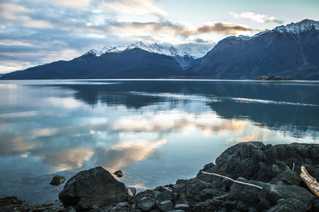 Sunset over the Chilkat Inlet near Haines Alaska with clouds reflected in the water.