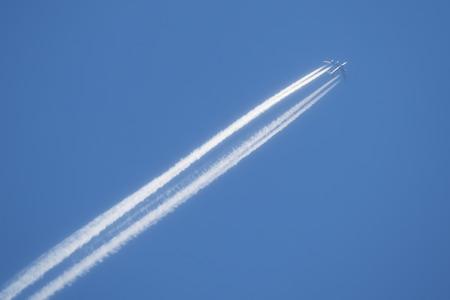 Jet with long vapor contrails against a blue sky.