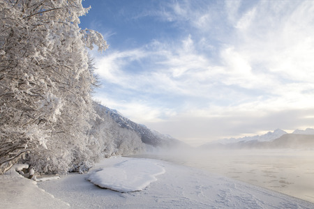 southeast alaska: Mist rising over the Chilkat River in Southeast Alaska with a snow covered beach and trees. Stock Photo