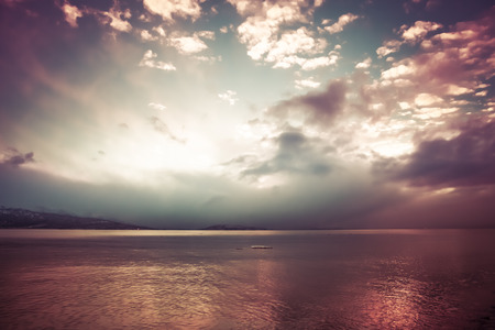 Brilliant sunset over the sea in pink and blue., enhanced with artistic coloration. Stock Photo