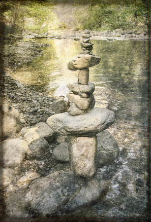 rock pile: Creative rock pile on the beach of a calm creek in summer with artistic textures overlaid.