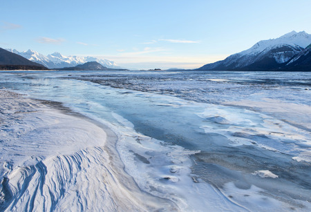 Wind sculpted snow patterns and frozen river ice on the Chilkat river near Haines Alaska on a sunny day. Stock Photo