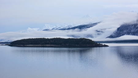 inlet: Fog near sunset on the Chilkat Inlet in Alaska with Koshu island and mountains in the background.