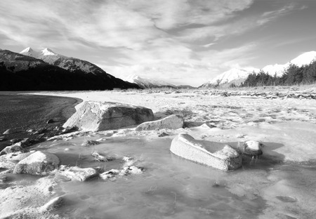 inlet: Ice chunks and snow on the beach of the Chilkat Inlet in winter in black and white.
