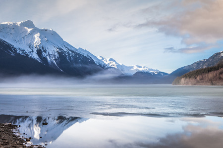 Ice melting on Chilkoot Lake near Haines Alaska with a mist rising off the lake and reflections in the water.