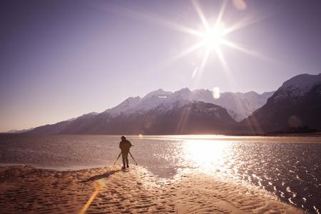 An Alaskan photographer on a sunny beach with a sunburst and lens flare.