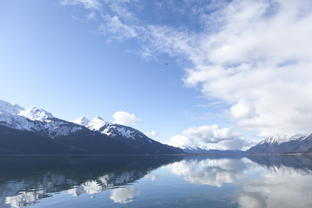 southeast alaska: Mountains and clouds reflected in the still water of the Chilkat Inlet in Southeast Alaska.