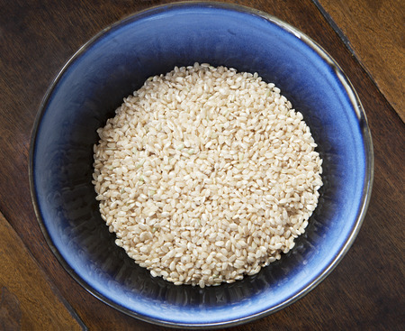 Blue bowl of uncooked brown rice on a wooden table.