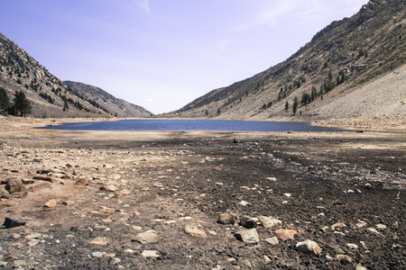 sierras: California lake with very low water from years of drought.