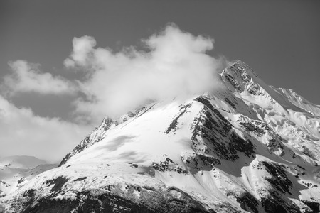 Chilkat mountains near Haines Alaska in early spring with snow and clouds in black and white.