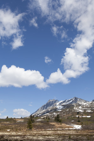 melts: High elevation mountains of British Columbia in spring as snow melts with clouds and blue sky. Stock Photo