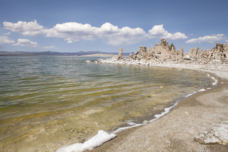sierras: Water lapping on a beach of Mono Lake on the eastern side of the Sierras in California on a warm day with clouds. Stock Photo
