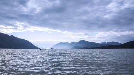 choppy: Kayak in rough water with storm clouds in the Chilkat Inlet near Haines Alaska in evening light.