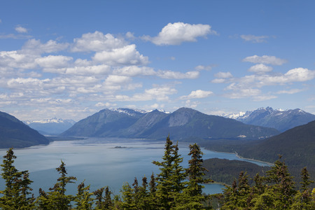 cicuta: View of the Chilkat Inlet near Haines Alaska from a mountain in summer with puffy clouds.
