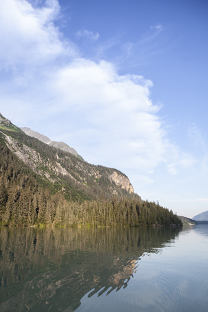 southeast alaska: Chilkooot Lake with mountains in Southeast Alaska in summer evening light with clouds and reflections.