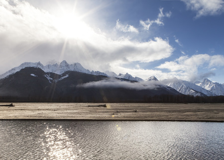 breaking free: Sun breaking free from clouds over Alaskan mountains near the Chilkat River.