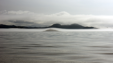 shrouded: Fog shrouded hills off the coast of British Columbia as seen from a boat in summer.