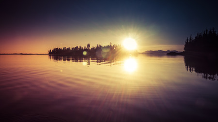southeast alaska: Sunset from an Island off the coast of Southeast Alaska with lens flare and coloration.