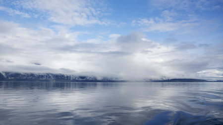 southeast alaska: Low clouds and fog covering coastal mountains in Southeast Alaska as seen from a boat in the Lynn Canal.