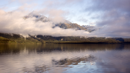 southeast alaska: Sunset from Sullivan Island in Southeast Alaska with fog clearing to reveal mountain peaks reflected in calm water.