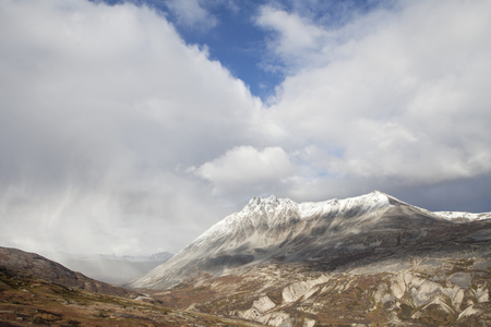 elevation: Storm clouds part to reveal sun on mountain peaks in high elevation British Columbia in fall. Stock Photo