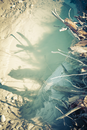 pool stick: Tangle of sticks casting crazy shadows on water and ice on a rivers edge. Stock Photo