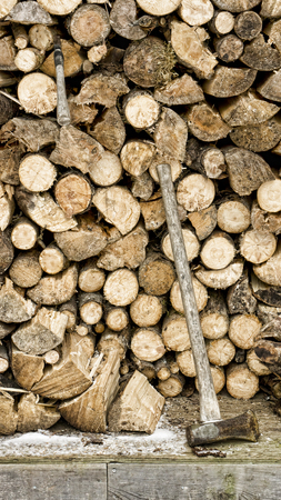 Full woodshed in winter with a splitting maul and hatchet. Stock Photo
