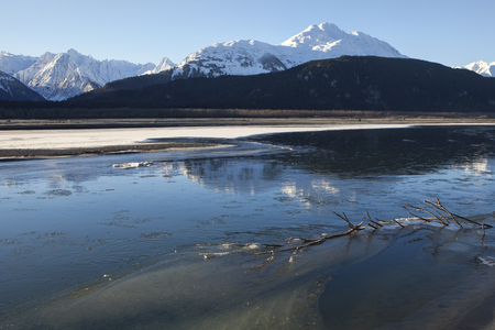 southeast alaska: Chilkat River in Southeast Alaska flowing in early winter with ice forming on a sunny day.