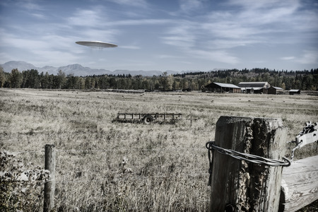 photomanipulation: UFO flying over farmland with buildings in the background colorized for a vintage look. Stock Photo