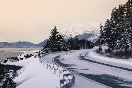 southeast alaska: Plowed road in Southeast Alaska near Haines with snow in evening light. Stock Photo