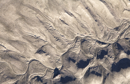 silt: Patterns formed by tidal water flows in beach sand silt in an Alaskan estuary close up. Stock Photo