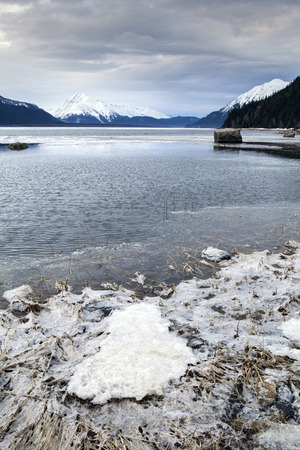 inlet: Dark storm clouds moving in over the Chilkat Inlet near Haines Alaska in winter with ice and open water.