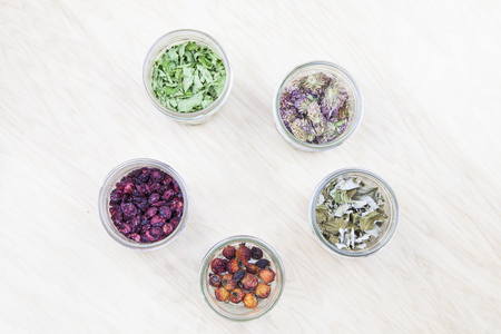 red clover: Flat lay photo of wildcrafted dried tea ingredients (mint, raspberry leaves, red clover, rose hips, cranberries) in jars on a wooden background.