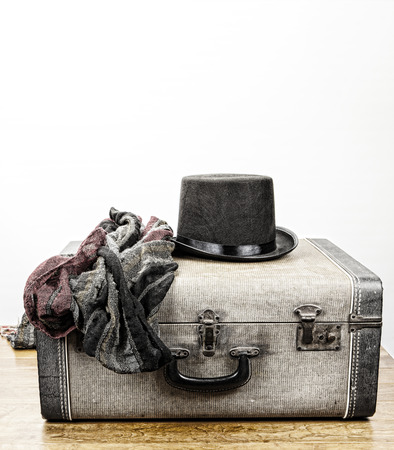 coloration: Top hat and scarf on a vintage accordion case on a wood floor with a white background for text processed with vintage coloration.