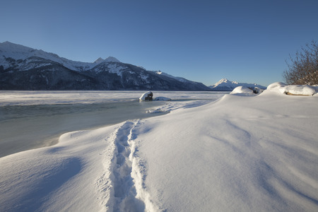 southeast alaska: Snowshoe path through wind sculpted snow to a frozen river on a sunny day in Southeast Alaska on the Chilkat River. Stock Photo