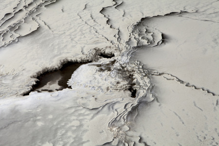 silt: River silt covering ice patterns after a dust storm for a natural abstract. Stock Photo