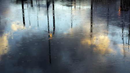 masts: Reflections of masts in a harbor with rain drops near sunset. Stock Photo