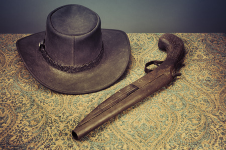 Antique leather hat and gun on a vintage table cloth with retro coloration. Stock Photo