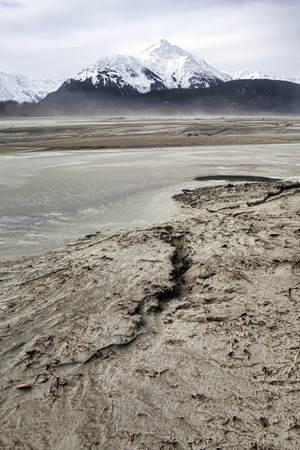 Chilkat river beach in Southeast Alaska during a windy dust storm with sculpted sand in the foreground. Stock Photo
