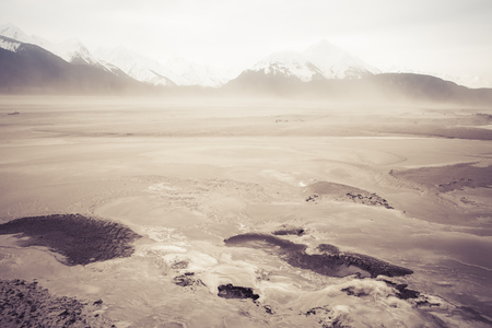 silt: Dust storm blowing river silt  on the Chilkat river near Haines Alaska with dust covering ice and mountains in the background. Stock Photo