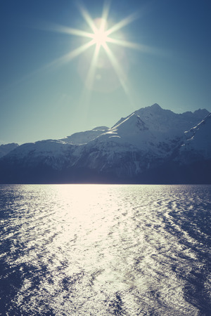 southeast alaska: Sunburst over mountains with the sea in the foreground in Southeast Alaska. Stock Photo